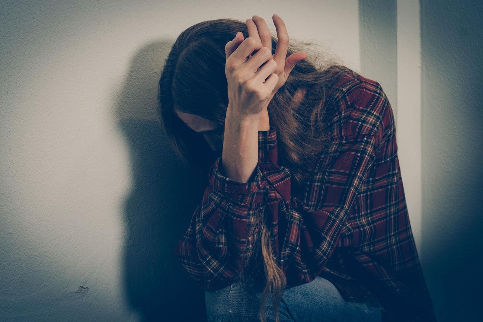 gewalt gegen frauen: Frau duckt sich ängstlich in eine ecke